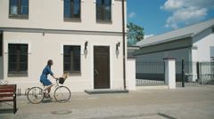 Side view of a brunette girl riding a bike near old buildings as people walk by - stock footage