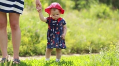 Adorable one year old Baby Girl making her first steps outdoor. First Steps of Stock Footage