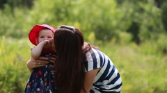 Mother is playing with her baby daughter outdoors. Young mom and her cute little Arkistovideo