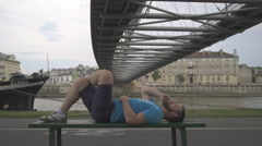 Man is talking by smatphone, lying on the bench against the river. Stock Footage