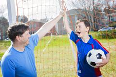 Man with  child playing football on  pitch Stock Photos
