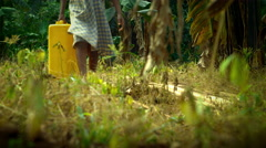 Child walking with jerrycans for water in Africa Stock Footage