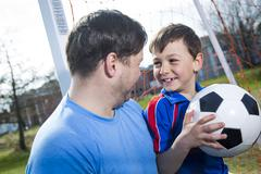 man with  child playing football on  pitch - stock photo