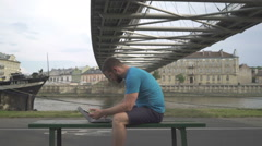Man is coping data from smartphone to laptop, sitting on the bench. Stock Footage