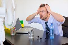 Flushed employee feeling hot in front of a fan Stock Photos