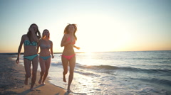three girls wearing bikini run along the  sea at sunrise slow motion - stock footage