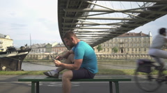 Man is browsing tablet, sitting on bench against the river. Stock Footage