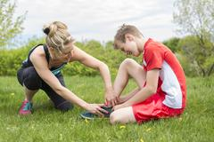 Athletic boy Holding her Painful Injured ankle Stock Photos