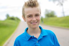 Young happy smiling male boy teenager blond child outside in summer sunshine Stock Photos