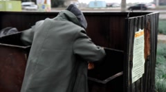 Homeless looking for food in garbage cans Stock Footage