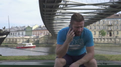Man is talking by smatphone, sitting on the bench against the river. Stock Footage