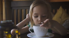 A little kid having breakfast at a cozy cafe. An adorable girl drinking tea and Stock Footage