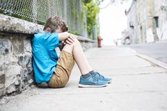 Photo of Sad and Stressed Kid sit by the Wall outdoor Stock Photos