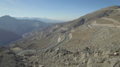 Curved road seen from top of rocky mountain Stock Footage