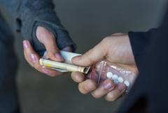 close up of addict buying dose from drug dealer - stock photo