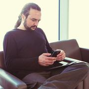 Handsome young man with dreadlocks using his phone at an airport lounge Stock Photos