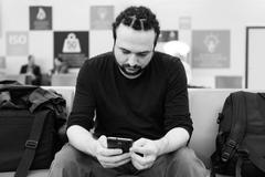 Handsome young man with dreadlocks using his phone at an airport lounge. Stock Photos