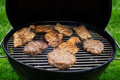 High angle view of succulent steaks and burgers cooking on a barbecue - stock photo