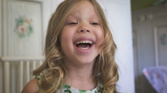 A beautiful little girl is smiling in the bright room Stock Footage