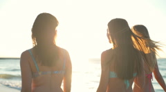 back view of three young women walking along the sea in sun light slow motion - stock footage