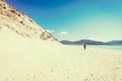 Young male photographer at a sunny white sandy beach with high dunes Stock Photos