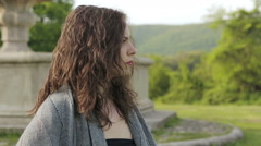 Sensual woman looks around in ancient park Stock Footage