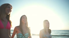 Close up three happy girlfriends in bikini walk along the sea slow motion Stock Footage