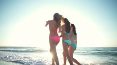 Back view joyful girls walking at the sea edge in sun light slow motion Stock Footage