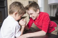 Brothers compete in arm wrestling Stock Photos