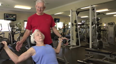 Mature Woman Working Out With Free Weights In Fitness Center Stock Footage