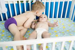 Cute Baby in Crib with his brother - stock photo
