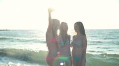 Smiling girls in bikini taking selfie in sun light on the beach slow motion Stock Footage
