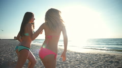Three happy girls running into the sea in sun light slow motion Stock Footage