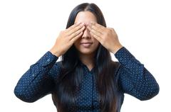 Young woman covering her eyes with her hands - stock photo
