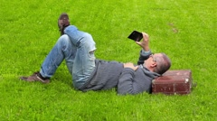 Man with suitcase sleeping on grass and take pictures on smart phone Stock Footage