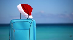 Santa Claus hat on suitcase at tropical sandy beach Stock Footage