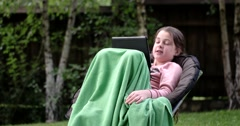 Little Girl Using Touchpad on Chair Outdoor and Make a Funny Face Stock Footage