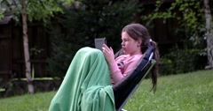 Little Girl Using Touchpad on Chair Outdoor Stock Footage