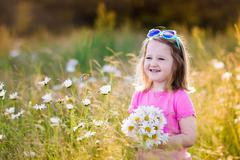 Little girl in daisy flower field - stock photo