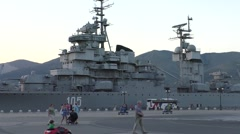 View of Big Grey Military Ship and Walking People on Seaport Stock Footage