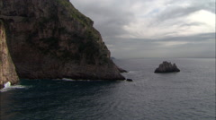 Small rocky island low on positano coast with waves crashing Stock Footage