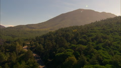 Hill covered in trees to reveal road leading towards mount vesuvius Stock Footage