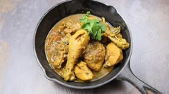 North Indian spicy chicken curry in a skillet - stock footage