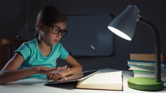 Close up portrait school girl 7-8 years using tablet pc in night and smiling Stock Footage