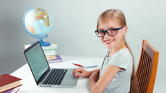 Portrait student 7-8 years old using laptop and sitting in the table Stock Footage