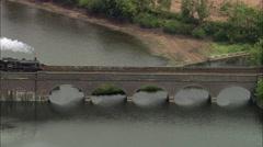Steam Train Passing Over Lake On Bridge Stock Footage