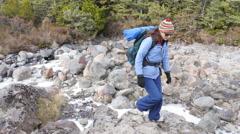 Woman hiker crossing a frozen stream Stock Footage
