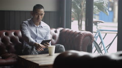 4K Pensive young man sitting alone in cafe looking at computer tablet Stock Footage