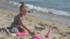 Little girl playing with toys on sand beach near wavy sea at sunny day by Sheyno Stock Footage