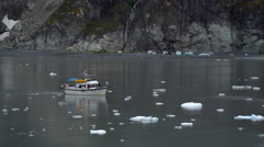 Boat floats through icy water with rock in background Stock Footage